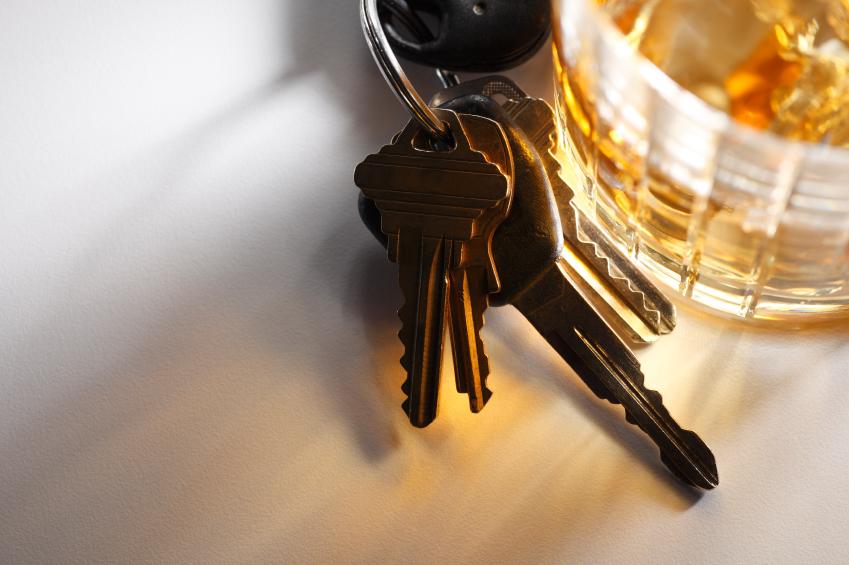 Car keys next to a glass of alcohol