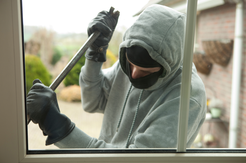 Burglar with crowbar trying to enter house
