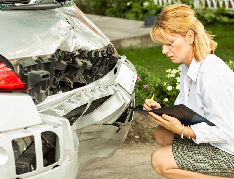 Woman inspecting car accident damage.